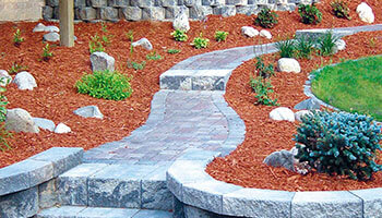 Well manicured landscaping with a stone walkway and retaining walls | Landscape Materials